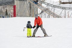 Toddler Boy Dressed Warmly & in Good Safety Gear Learns to Ski with his Dad royalty free stock photo