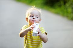 Toddler boy drinking milk or juice Stock Image