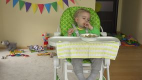 Toddler boy eat mash with spoon sitting in baby high feeding chair stock video footage