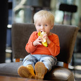Toddler boy eating banana Stock Photography