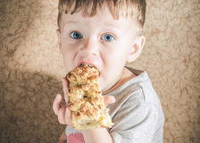 Toddler boy eating a big piece of pie Royalty Free Stock Images