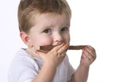 Toddler boy eating chocolate Stock Image