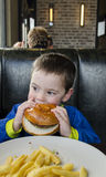 Toddler boy eating Hamburger and fries Royalty Free Stock Photos
