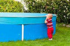 Toddler boy exploring garden swimming pool Royalty Free Stock Images