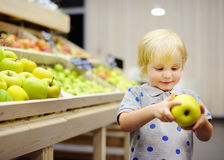 Toddler boy in a food store or a supermarket choosing fresh apples Stock Photography