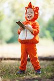 Toddler boy in fox costume holding smartphone Stock Photos