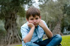 Toddler boy with funny face sad or bored. He sitting alone at park on autumn day royalty free stock images
