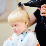 Toddler boy getting his first hairstyle. Portrait of toddler boy getting his first hairstyle Stock Photography