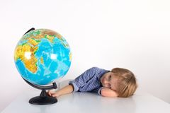 Toddler boy with a globe on the lesson of practical life on a white background, Montessori class, isolate. Toddler boy with a globe on the lesson of practical royalty free stock photo