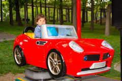 Toddler boy having fun in a car in park Stock Photo