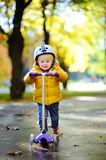Toddler boy in helmet to ride scooter Stock Photo