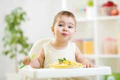 Toddler boy in a highchair for feeding with a fork Royalty Free Stock Image