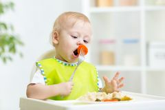 Toddler boy in a highchair for feeding with a fork Royalty Free Stock Photos