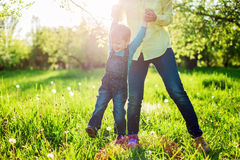 Toddler boy and his mom having fun in summer park,. Image with backlight, some stay light in foreground Royalty Free Stock Images