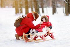 Toddler boy and his mother having fun in winter park. Portrait of beautiful toddler boy and his mother having fun in winter park. Family game with fresh snow Stock Photo