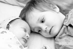 Toddler boy with his newborn sister royalty free stock photo