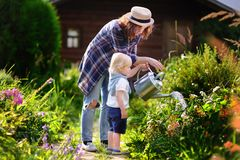 Toddler boy and his young mother watering plants in the garden. Cute toddler boy and his young mother watering plants in the garden at summer sunny day Stock Photo