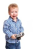 Toddler boy holding camera and crying Stock Photo