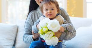 Toddler boy holding flowers Stock Photo