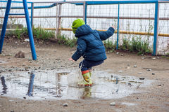 Toddler boy jumping in the puddles. In rubber boots Stock Images