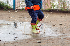 Toddler boy jumping in the puddles royalty free stock photo