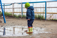 Toddler boy jumping in the puddles. In rubber boots Stock Photo