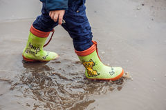 Toddler boy jumping in the puddles. In rubber boots Royalty Free Stock Photo