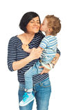 Toddler boy kissing his mother. Toddler standing in his mother arms and kissing her cheek isolated on white background royalty free stock photos