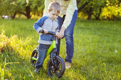 Toddler boy learning to ride his first bike. Royalty Free Stock Images
