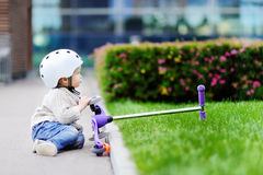 Toddler boy learning to ride scooter Royalty Free Stock Photos