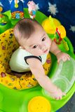 Toddler boy learning to walk in funny babywalker. With toys royalty free stock photos