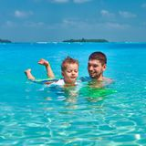 Toddler boy learns to swim with father stock photo