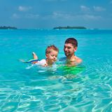 Toddler boy learns to swim with father stock photos