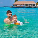 Toddler boy learns to swim with father royalty free stock image