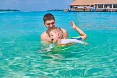 Toddler boy learns to swim with father stock images