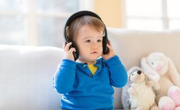 Toddler boy listening to music with headphones. Toddler boy listening to music with big headphones royalty free stock images