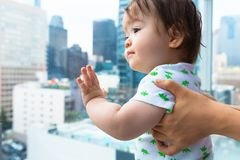 Toddler boy looking out at the city a glass balcony. Toddler boy looking out at Downtown Los Angeles from a glass balcony Stock Photography