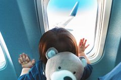 Toddler boy looking out a plane window stock images