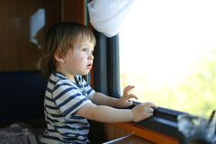 Toddler boy looking out of window in the train Royalty Free Stock Photos