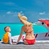 Toddler boy with mother sitting on wooden jetty stock photos