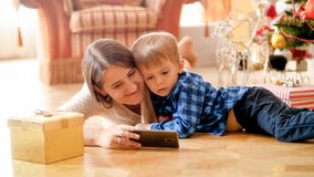 Little toddler boy with mother watching cartoons on phone on Christmas morning. Toddler boy with mother watching cartoons on phone on Christmas morning royalty free stock photo