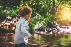 Toddler boy in nature near water royalty free stock photo