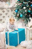 Toddler boy opening a box with Christmas gift Stock Photo