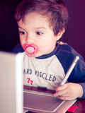 Toddler boy with pacifier  in front of a notebook Stock Image