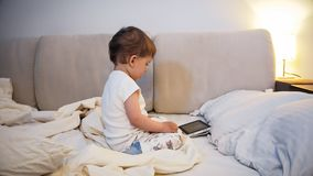 Adorable toddler boy in pajamas sitting o nbed at night and watching cartoons on digital tablet royalty free stock photography