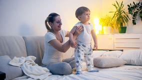 Cute toddler boy in pajamas with young smiling mother in bed before going to sleep. Toddler boy in pajamas with young smiling mother in bed before going to sleep Stock Images