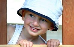 Toddler boy peeking out of window. Toddler boy with white hat stock photo