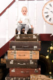 Toddler boy on pile of suitcases. Near banister indoors Royalty Free Stock Image