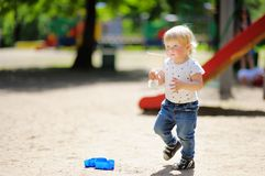 Toddler boy on playground. Beautiful toddler boy with scoop on playground Royalty Free Stock Image