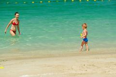 Toddler boy playing on beach with mother. Two year old toddler boy playing on beach with mother Royalty Free Stock Image
